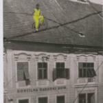 A man walking on rope between houses